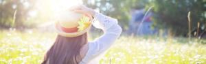 Frau, die auf einer schönen Wiese ihren Hut hält und die Sonne geniesst
